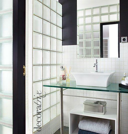 Un baño con muros de pavés, decorado en blanco y negro